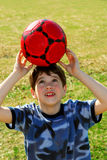 Boy with soccer ball. Young cute happy boy balancing a red soccer boy on his head outside Stock Photos