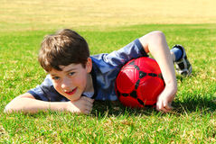 Boy with soccer ball. Young cute happy boy lying on grass with red soccer ball stock images