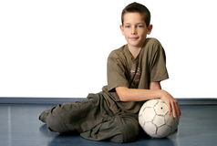 Boy With Soccer Ball. Sitting boy with soccer bal. The main focus is on the boy's face Stock Photos