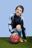 Boy with soccer ball on blue background Royalty Free Stock Photography