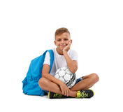 A boy with a soccer ball and a blue satchel sitting in a joga pose. Happy child isolated on a white background. Sports royalty free stock photography