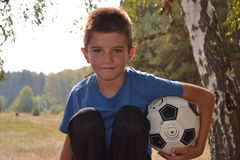 Boy with a soccer ball. In a forest in autumn Royalty Free Stock Photos