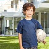 Boy with soccer ball in garden Stock Photo