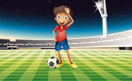 A boy with a soccer ball standing in the soccer field Stock Photo