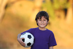 Boy with soccer ball at sunset royalty free stock photography