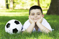 BOY WITH SOCCER BALL. Young cute happy boy lying on grass with soccer ball Royalty Free Stock Image