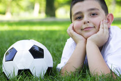 BOY WITH SOCCER BALL. Young cute happy boy lying on grass with soccer ball Stock Photos