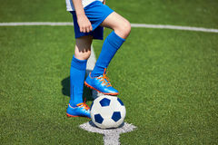 Boy soccer in football boots with ball on grass Stock Photos
