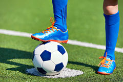 Boy soccer in football boots with ball on grass Royalty Free Stock Images
