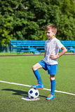 Boy soccer in football boots with ball on grass. Foot of a soccer player in a football boot on a ball on an artificial green lawn of the stadium Royalty Free Stock Image