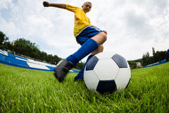 Boy soccer player hits the ball Royalty Free Stock Image