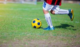 Boy soccer player speed run to shoot ball to goal on green grass. Soccer player training or football match stock photo