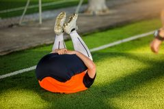 Boy soccer player stretch muscles with lying back stock image