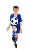 Boy soccer skills. A boy using a soccer ball skills practice.  Ball has some motion.  White background Royalty Free Stock Image