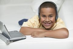 Boy on sofa Watching movie on DVD Player Stock Images