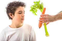 Boy with soft skin is puzzled in front of vegetables Stock Photo