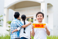 Boy with sold sign. Little boy with sold sign on the background of his parents looking at the house royalty free stock images