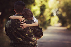 Boy and soldier in a military uniform Stock Photos