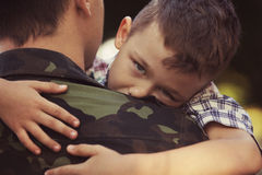 Boy and soldier in a military uniform. Say goodbye before a separation Royalty Free Stock Photography