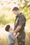 Boy and soldier in a military uniform. Say goodbye before a separation stock image