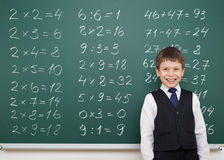 Boy solve math on school board. Boy with math numbers on school board Royalty Free Stock Photography