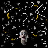 Boy solve mathematics examples at the blackboard. On black background royalty free stock images