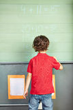 Boy solving math problem on chalkboard Royalty Free Stock Photography