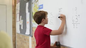 Boy solving math problem at whiteboard. Rear view of young boy solving addition and subtraction on white board at school. Schoolboy thinking while solving math`s stock footage