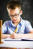 Boy solving math problems at home. Alone Royalty Free Stock Image