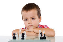 Boy solving a problem. Concentrated little boy solving a problem playing chess - isolated stock photos