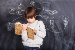 Boy solving puzzles. Thoughts of children against the black chalkboards Royalty Free Stock Image