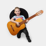 Boy in sombrero with guitar on gray. Boy in sombrero stays on knee with big guitar on gray background in square Royalty Free Stock Photo