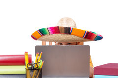 Boy in sombrero surrounded by books and laptop Royalty Free Stock Photography