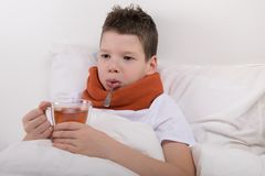 Boy with a sore throat he drinks warm tea, with honey right in his bed Royalty Free Stock Photography