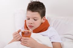 Boy with a sore throat, is treated with warm tea. A boy with a sore throat, is treated with warm tea Stock Image