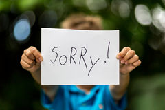 Boy with Sorry sign. Blurred boy holding a piece of paper with the word Sorry in front of her stock photography