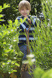 Boy With Spade Surrounded By Plants Stock Images