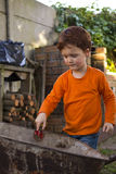 Boy with spade and wheelbarrow Stock Photo