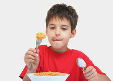 A boy and spaghetti. A boy licking while eating spaghetti with fork and spoon isolated on a white background Royalty Free Stock Images