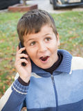 Boy speaking at the phone. A little boy speaking at the phone and having a surprised expression Royalty Free Stock Photo