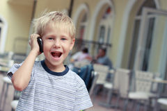Boy speaks to a mobile phone. Stock Photo