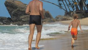 Boy spends time with daddy running along beautiful beach
