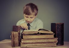 The boy spends time reading old books Royalty Free Stock Images