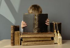 The boy spends time reading old books Stock Photo