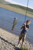 The boy with a spinning catch grayling Stock Image