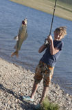 The boy with a spinning catch grayling Royalty Free Stock Photos