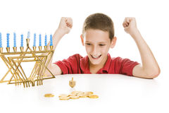 Boy Spinning the Chanukah Dreidel. Cute little boy on Chanukah playing with his dreidel. Isolated on white with menorah and gelt royalty free stock images