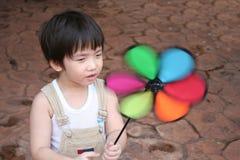 Boy & spinning windmill Stock Photos