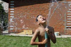 Boy with splash water in hot summer day Royalty Free Stock Photos