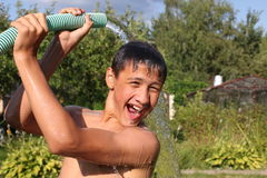 Boy with splash water in hot summer day outdoors Stock Photography